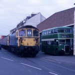 The train that ran on the road: 'Class 33' No. 33116 eases its way along Weymouth Quay past a Hants & Dorset 'Bristol' double-decker in August 1987 on a boat train connecting with the Channel Islands ferry.